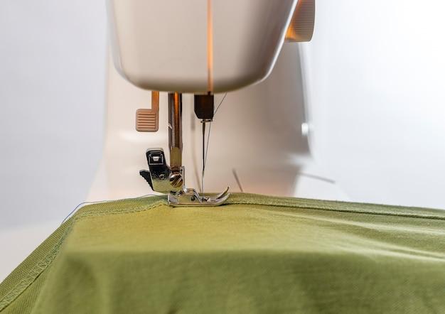 Close up de tecido verde natural sob a agulha da máquina de costura