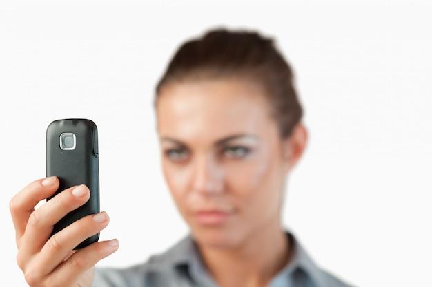 Close up de telefone celular sendo ocupado por empresária