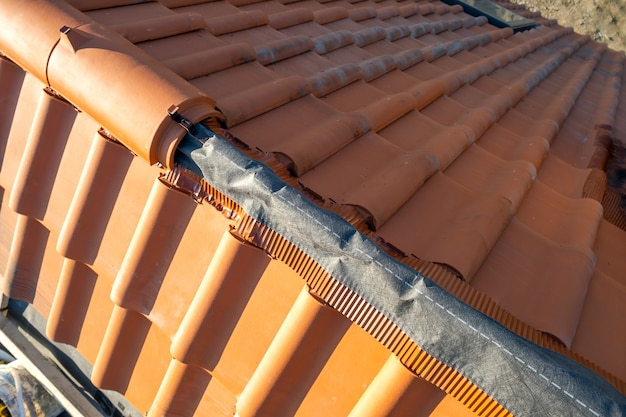 Close up de telhas de cume cerâmicas amarelas em cima do telhado de edifício residencial em construção.