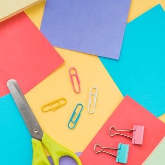Close-up de tesoura; clipe de papel e nota auto-adesiva colorida
