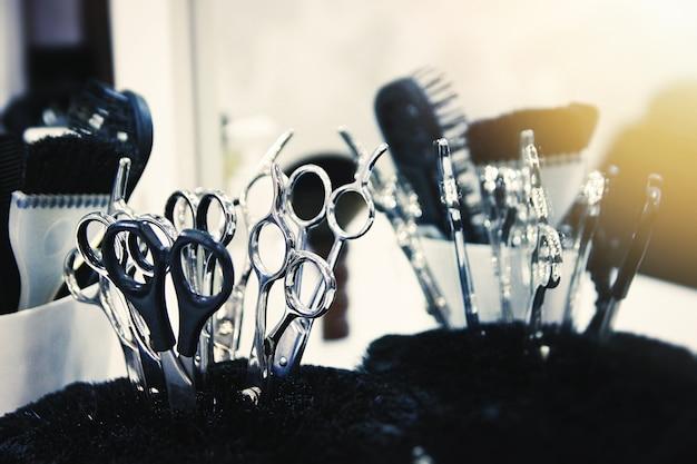 Close-up de tesouras e pincéis em um carrinho. ferramentas de salão de beleza. foco seletivo suave. brilho da lente