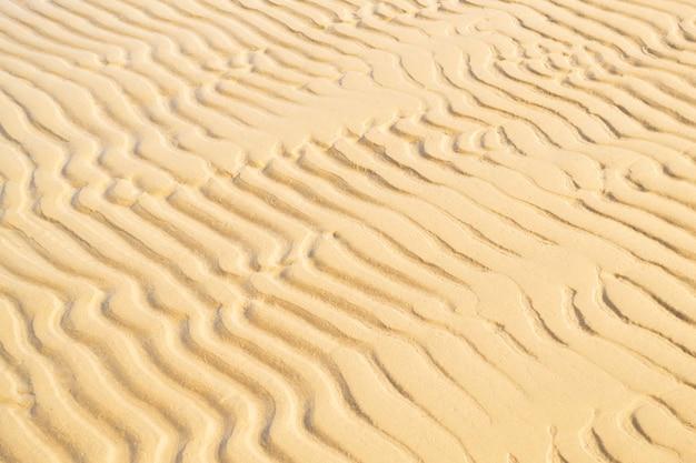 Close-up de textura ondulada de areia. plano de fundo da costa do mar. conceito de verão e férias. vista superior, copie o espaço.