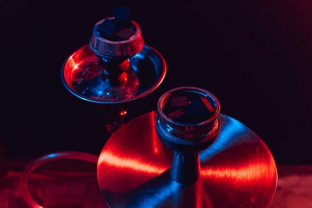 Close-up de tigela de narguilé, shisha e carvão em um fundo preto com iluminação colorida