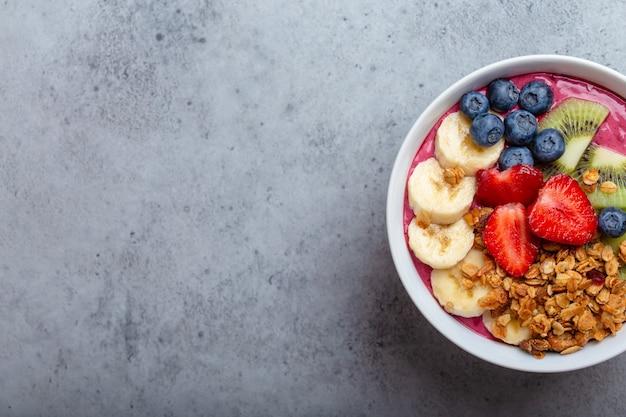Close-up de tigelas de suco de açaí de verão com morangos, banana, mirtilos, kiwis e granola em fundo cinza de concreto. tigela de café da manhã com frutas e cereais, vista de cima, espaço para texto