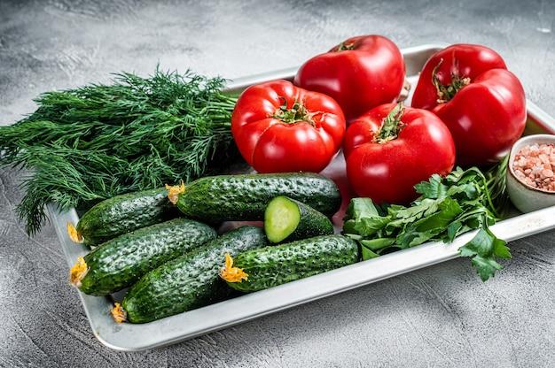 Close up de tomates vermelhos e pepinos verdes com ervas em uma bandeja da cozinha. fundo branco. vista do topo.