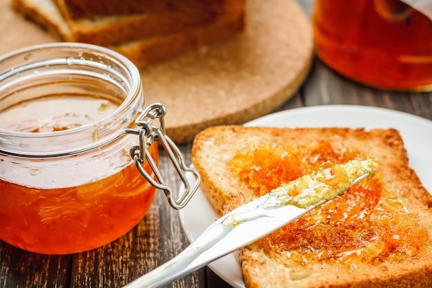 Close up de torrada com geléia de laranja caseira em uma tabela