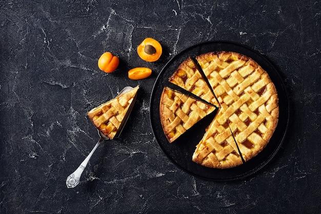 Close-up de torta de crosta de damasco fatiada com cobertura de crosta de torta em um prato preto, uma fatia de torta em uma pá de bolo vintage em uma mesa de concreto, disposição plana, espaço livre