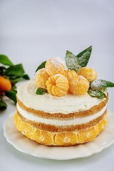 Close up de torta de frutas cítricas com tangerina fresca e folhas verdes