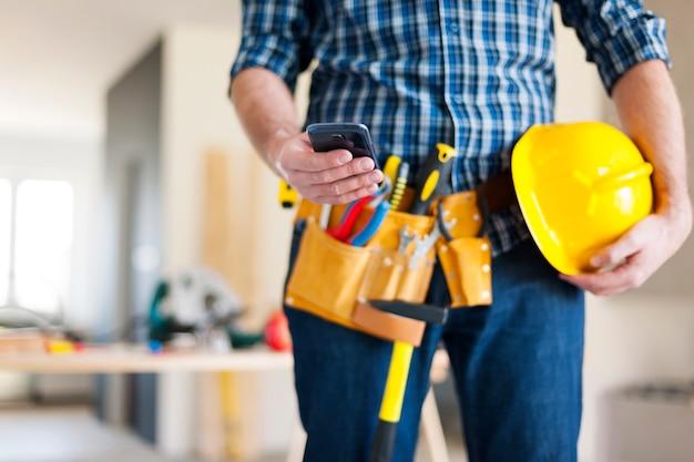 Close-up de trabalhador da construção civil com telefone celular