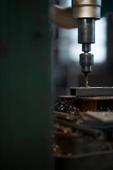 Close-up de trabalhador fazendo furos em metal em tornos chatos