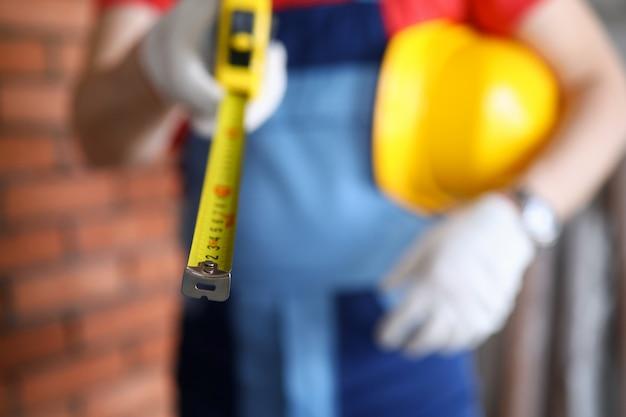 Close-up de trabalhador manual segurando a roleta e capacete amarelo. equipamento necessário para o trabalho. capataz de uniforme. artesão profissional. local de construção e conceito de renovação
