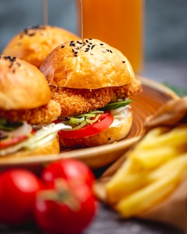 Close-up de três mini hambúrgueres servidos com batatas fritas em caixa de papel