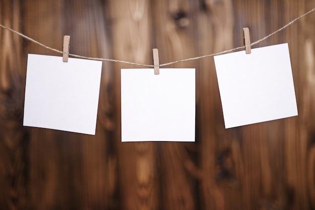 Close-up de três papéis de nota branco pendurados por cabides de madeira sobre um fundo marrom de madeira