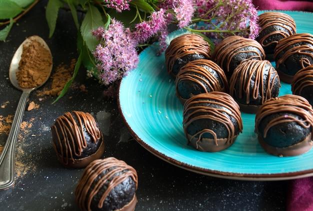 Close up de trufas de chocolate em colher de prato azul com sobremesa doce de cacau em pó