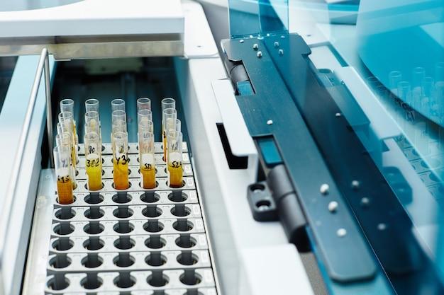 Close-up de tubos de ensaio com líquidos amarelos em linhas na caixa com marcas pretas