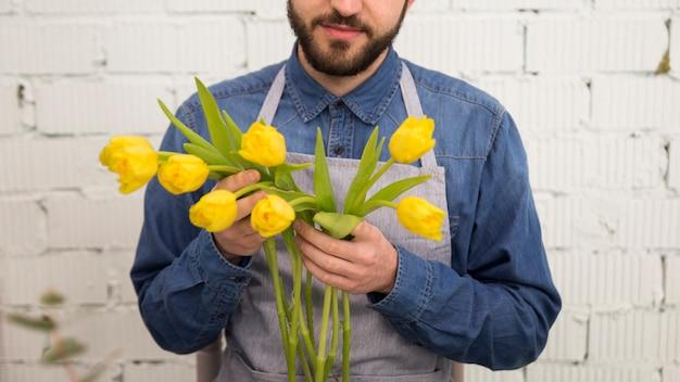 Close-up de turista masculina segurando as tulipas amarelas na mão de pé contra a parede branca