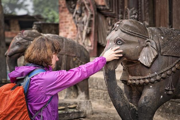 Close-up de turista ocidental, apoiando a mão na cabeça em ganesha, airavata, para fazer um pedido de oração.