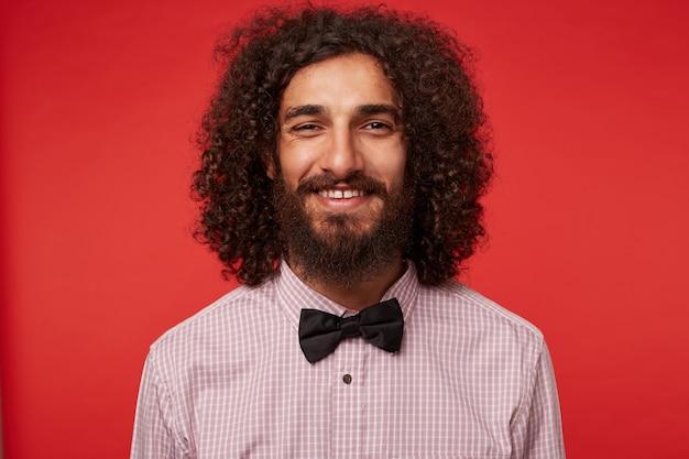Close-up de um adorável jovem de cabelos escuros e barbudo encaracolado em roupas elegantes, com um sorriso encantador e mostrando seus dentes brancos perfeitos, isolado