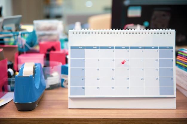 Close-up de um alfinete no calendário de mesa em branco.