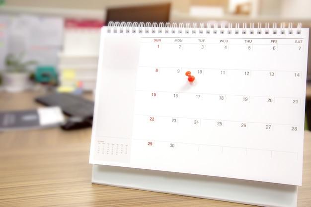 Close-up de um alfinete vermelho no calendário de mesa em branco. Foto Premium