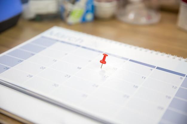 Close-up de um alfinete vermelho no calendário de mesa em branco.
