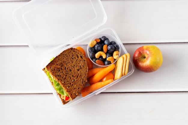 Close-up de um almoço escolar saudável e vegan com sanduíche, frutas, cenouras e nozes