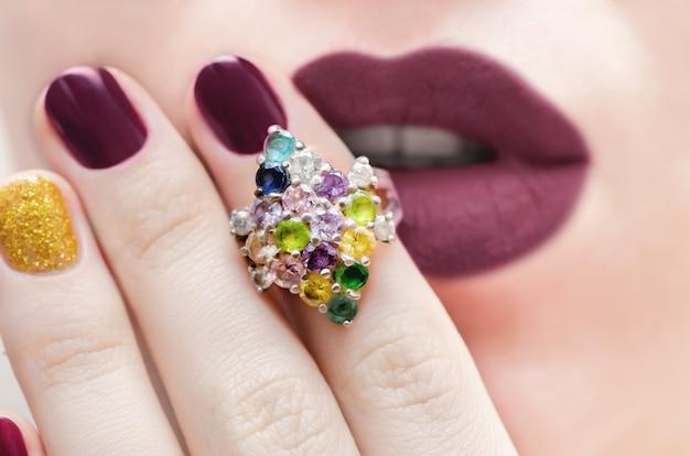 Close up de um anel de prata elegante com pedras preciosas de cor.