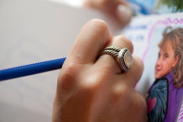 Close-up de um anel em uma mão, desenhando uma foto