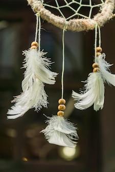 Close up de um apanhador de sonhos com penas brancas