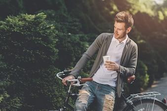 Close-up, de, um, assento homem, ligado, bicicleta, com, descartável, xícara café