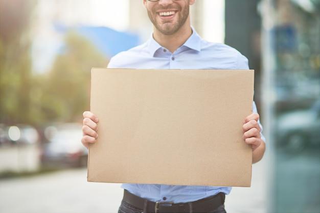 Close-up de um ativista sorridente, vestindo camisa azul e óculos, segurando uma placa vazia