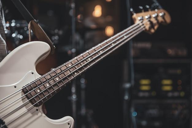 Close-up de um baixo nas mãos de um músico no processo de tocar.