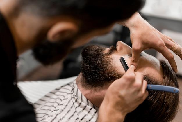 Close-up, de, um, barbeiro, mão, corte, cabelo homem, com, navalha