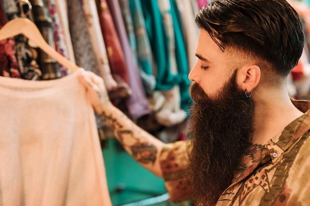 Close-up, de, um, barbudo, homem jovem, escolher, t-shirt, de, a, loja
