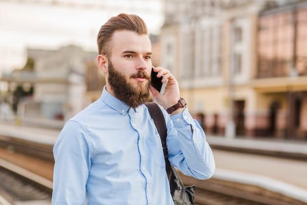Close-up, de, um, barbudo, homem jovem, usando, telefone móvel, em, estação de comboios
