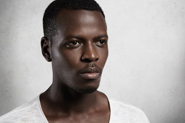 Close-up de um belo homem de pele escura parecendo sério e pensativo na parede em branco