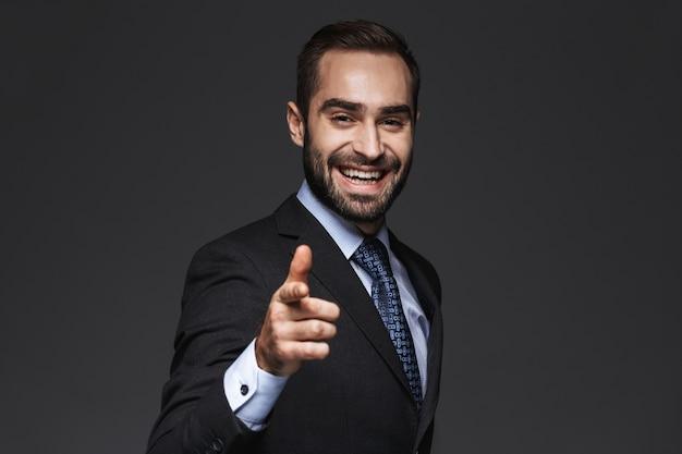 Close-up de um belo jovem sorridente homem de negócios vestindo terno, isolado, apontando para a frente