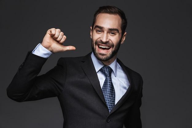 Close-up de um belo jovem sorridente homem de negócios vestindo terno, isolado, apontando para si mesmo