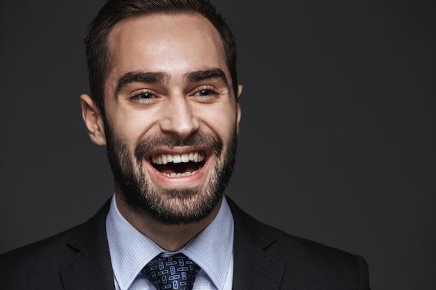 Close-up de um belo jovem sorridente homem de negócios vestindo terno, isolado, olhando para longe