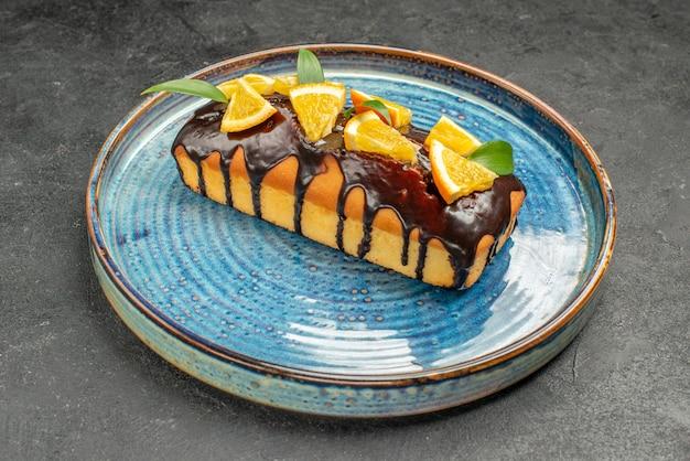 Close up de um bolo macio decorado com laranja e chocolate na mesa escura
