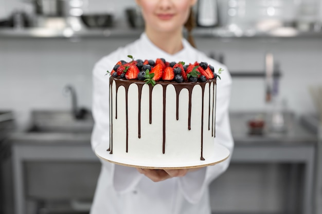 Close-up de um bolo nas mãos de um chef pasteleiro.
