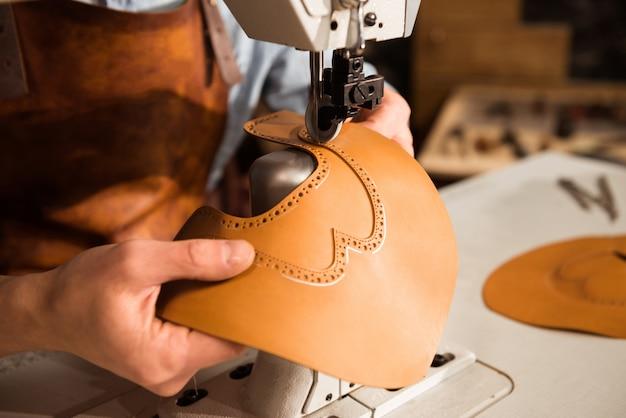 Close up de um bootmaker trabalhando com têxteis de couro