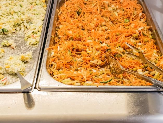 Close-up de um buffet de saladas com saladas de vegetais de cenoura e milho.