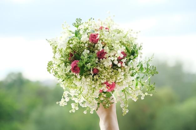 Close-up de um buquê de flores frescas de rosa e lírio do vale na mão de uma mulher