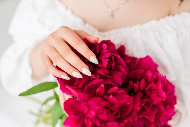 Close-up de um buquê de peônias nas mãos de uma menina. menina de vestido branco segurando flores vermelhas