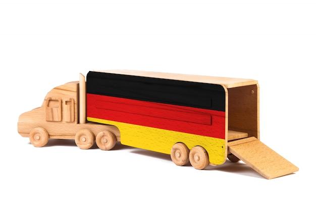 Close-up de um caminhão de madeira do brinquedo com uma bandeira nacional pintada alemanha. o conceito de exportação-importação, transporte, entrega nacional de mercadorias