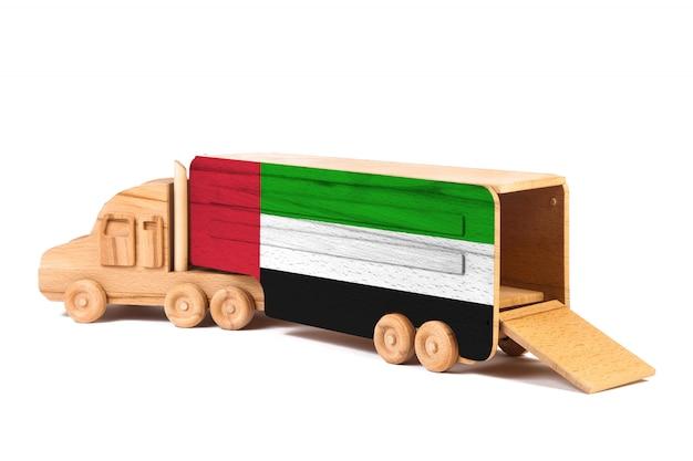 Close-up de um caminhão de madeira do brinquedo com uma bandeira nacional pintada nos emirados árabes unidos. o conceito de exportação e importação, transporte, entrega nacional de mercadorias