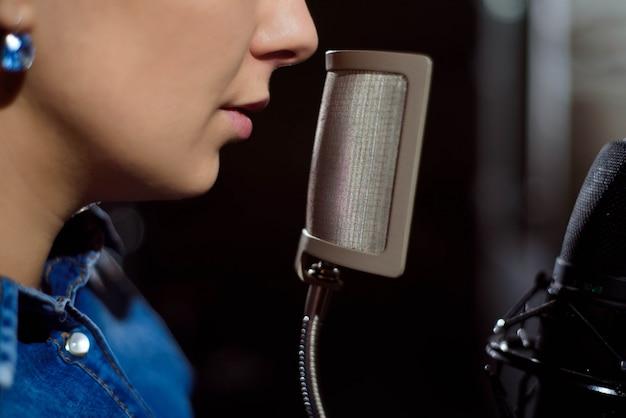 Close up de um cantor gravando uma faixa em um estúdio