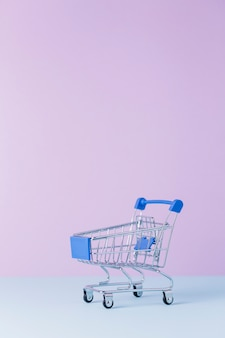 Close-up de um carrinho de compras vazio na frente do fundo rosa