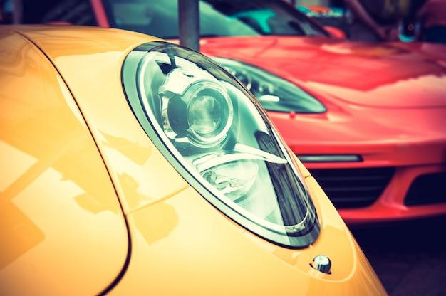 Close up de um carro esporte amarelo: faróis